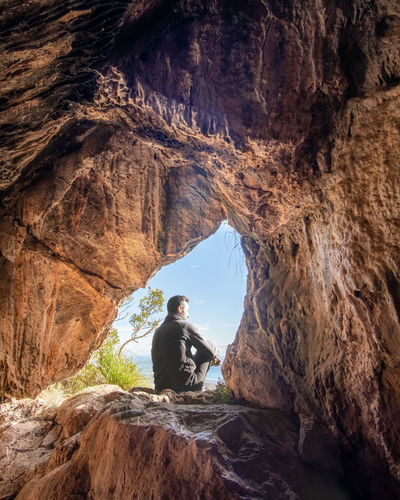 Man sitting on rock in cave