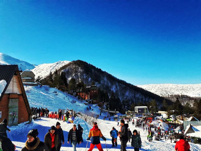 People in snow covered mountain against blue sky