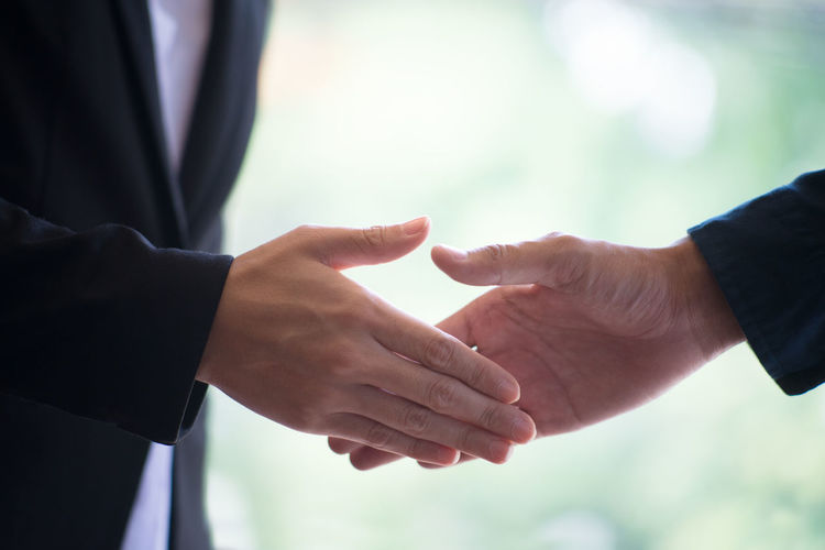 Midsection of businessman and colleague shaking hands at office