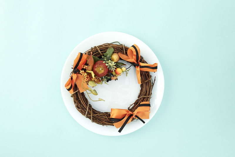 Empty dish with decorative wreath Halloween on pastel pale blue background, with copy space. Flat lay. Sales Holiday Flyer Banner Poster Travel Traveling Traveler Vacation Trip Sale Template Mockup Abstract Art Autumn Leaves Falling 2019 2020 Wreath New Year Halloween Autumn Leaves Autumn Background Plate Minimal Flat Lay Fall Background Leaf Design Frame Orange Concept Composition Green Maple Bright Pattern Forest Decoration Food And Drink Food Studio Shot Indoors  Wellbeing Healthy Eating Still Life Directly Above Freshness Bowl High Angle View No People Ready-to-eat Copy Space Table Vegetable Blue Colored Background Eating Utensil Serving Size