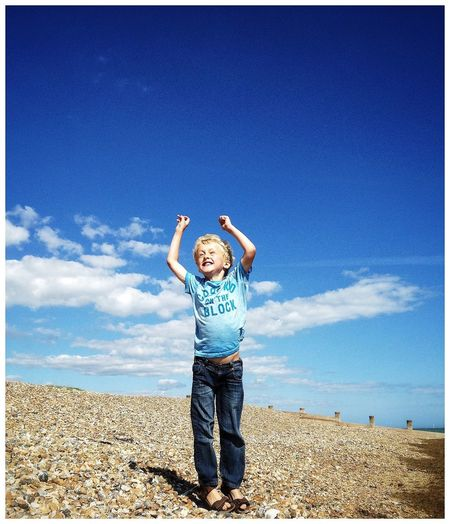 Portrait of boy standing on beach against blue sky
