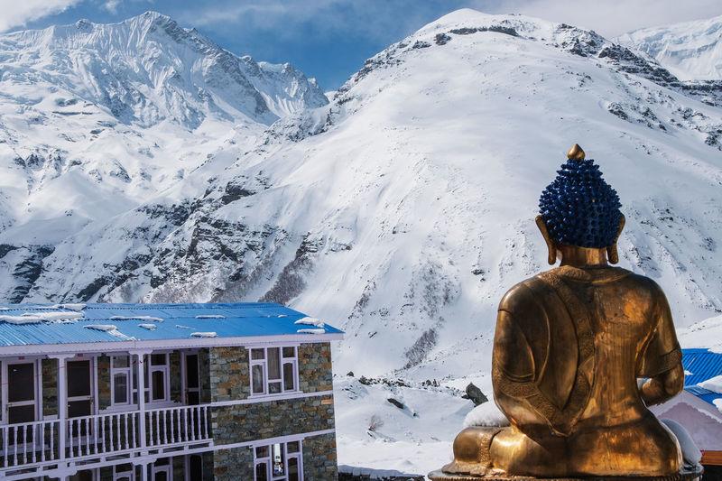 Buddha statue against snowcapped mountain