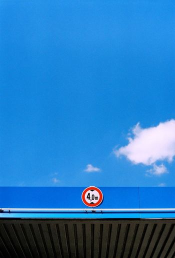 Low Angle View Of Number On Gas Station Against Blue Sky