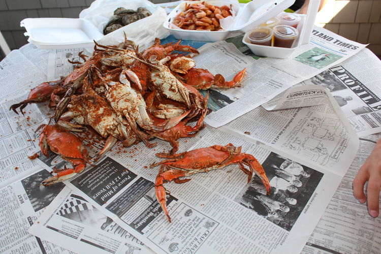 Cropped hand by crabs on table