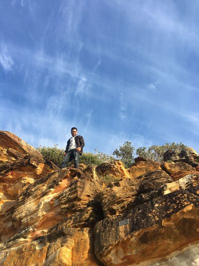Low Angle Portrait Of Young Man Standing On Rock Against Blue Sky During Sunny Day