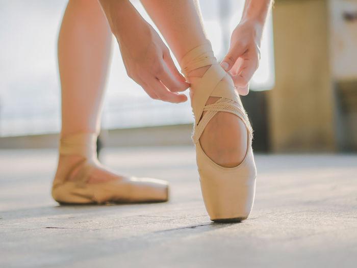 Low Section Of Ballet Dancer Wearing Shoe In Studio