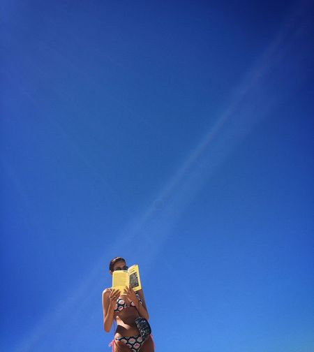 Arms Raised Blue Clear Sky Copy Space Day Hand Holding Human Arm Human Hand Leisure Activity Lifestyles Low Angle View Men Nature One Person Outdoors Photography Themes Real People Sky Standing Sunlight Technology