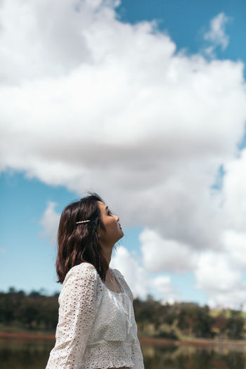 Woman looking away against sky