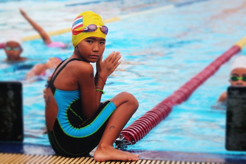 Because the water in the pool is very cold, do not go down to swim. Child Daughter Girl Portrait EyeEm Selects Swimming Pool Water Swimming Cap Swimming Goggles Real People Swimming Lane Marker Sport Strength Skill  Exercising Lifestyles Challenge Outdoors Swimming