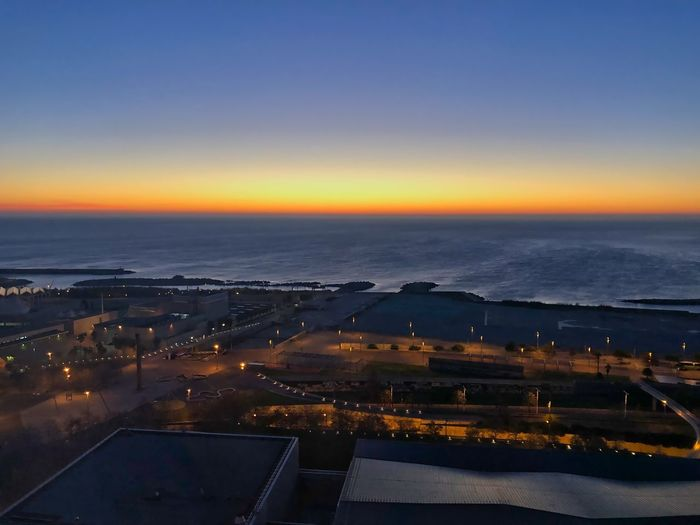 High angle view of illuminated buildings by sea against sky during sunset