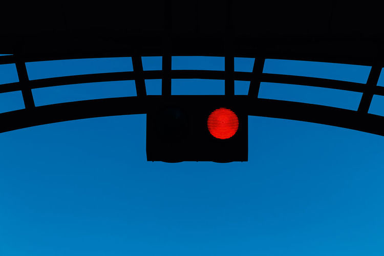 Low Angle View Sky No People Blue Red Light Light Nature Clear Sky Stoplight Red Outdoors Lighting Equipment Safety Illuminated Road Signal Sign Day Guidance Copy Space Architecture Directly Below Red Sign Not Allowed Prohibition
