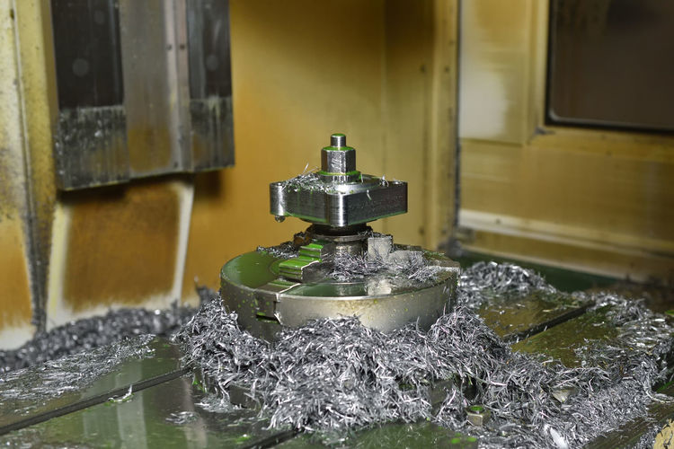Spindle chuck and installed metal part on high precision Cnc industrial lathe turning machine. metal chips Cnc Detail Lathe Machining Metal Turning Accuracy Alloy Chuck Coolant Cooling  Cut Cutter Equipment Factory Finishing Holder Industrial Machine Manufacture Milling Process Processing Production Shaping Spindle Steel Technology Tool Work Workshop precision Mill Automate Close Up Engine Engineer Handles Iron Machinery Measurement Part Quality Shaft Tooling Spindles Shavings Swarf Chips