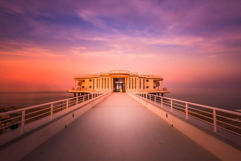 Architecture over sea against sky during sunset