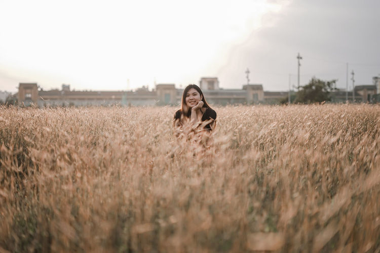 Young woman looking away standing in field