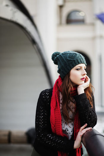 Portrait of young woman looking away while standing in winter
