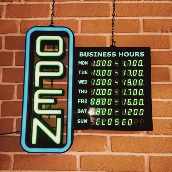 Low angle view of illuminated open sign by brick wall