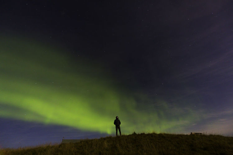 Silhouette Man Standing On Field Against Aurora Borealis At Night