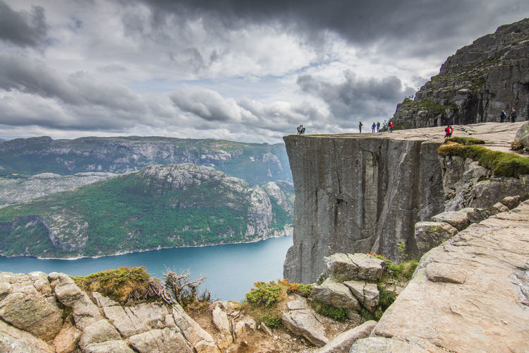 View on cliff and Fjord against cloudy sky Lysefjord Norway Preikestolen Beauty In Nature Cliff Cloud - Sky Day Environment Fjord Formation Mountain Mountain Range Nature Non-urban Scene Outdoors Rock Rock - Object Rock Formation Scenics - Nature Sky Solid Tranquil Scene Travel Travel Destinations Water