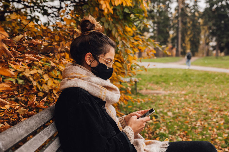 Woman wearing mask using smart phone sitting on bench
