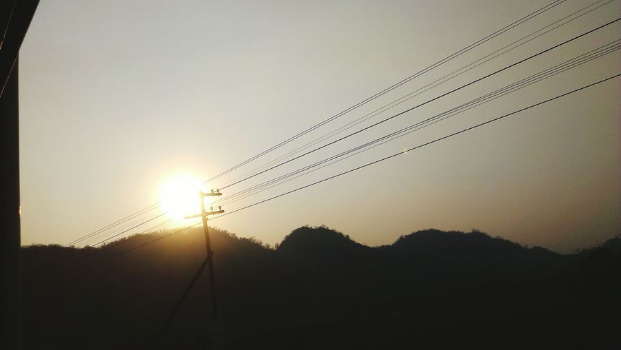 Silhouette electricity pylon against clear sky during sunset