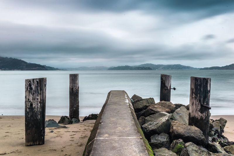 Sea Water Sky Nature Pier Cloud - Sky Beauty In Nature Tranquility Built Structure Horizon Over Water Tranquil Scene Day No People Scenics Wood - Material Wooden Post Outdoors Mountain Architecture Beach