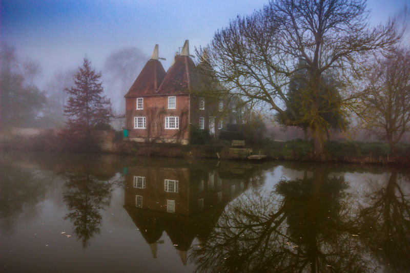 Reflection of houses in lake during foggy weather
