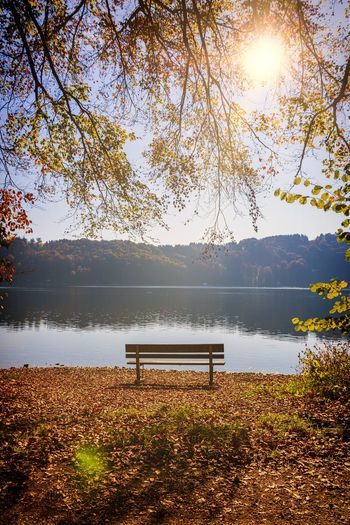Empty bench by lake against sky during autumn