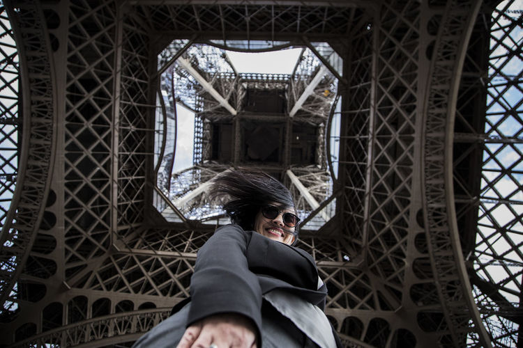 Directly below view of woman standing under eiffel tower