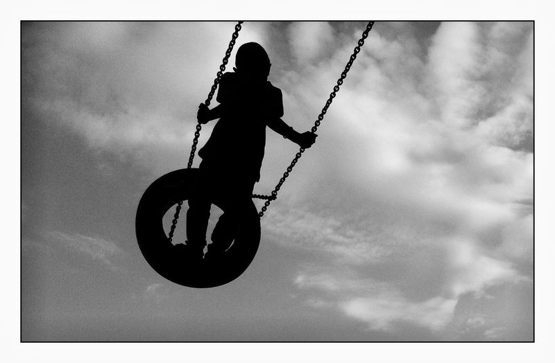 Silhouette boy swinging on tire swing against sky