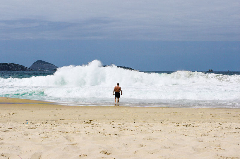 Rear view of shirtless man standing by waves in sea