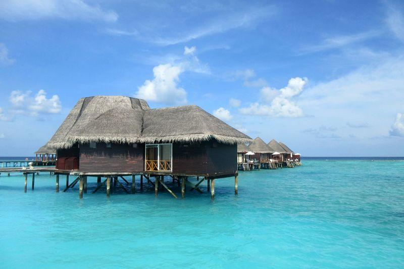 Stilt house over sea against blue sky