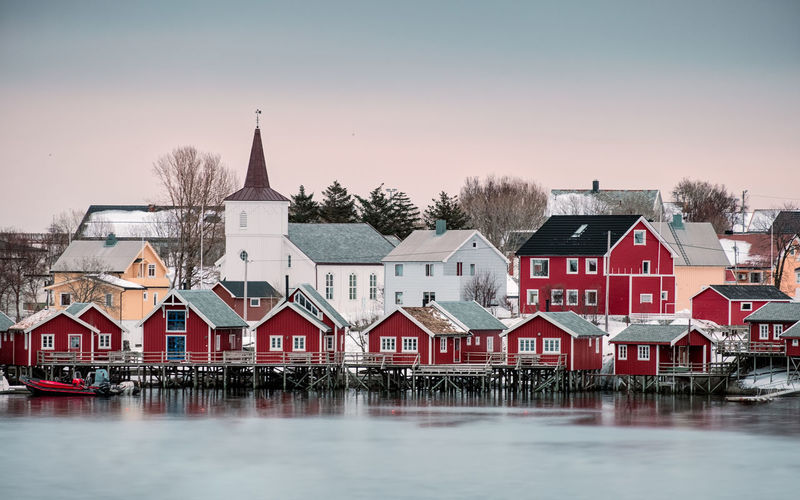 Houses by river against buildings in city during winter