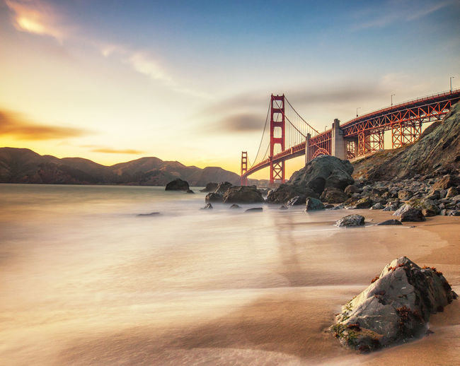 golden sunset on the golden gate bridge in san francisco Architecture Bay Bay Of Water Beauty In Nature Bridge Bridge - Man Made Structure Built Structure Cloud - Sky Connection Golden Sunset Light On The Golden Gate Bridge Mountain Nature No People Outdoors Sea Sky Sunset Suspension Bridge Transportation Travel Travel Destinations Water