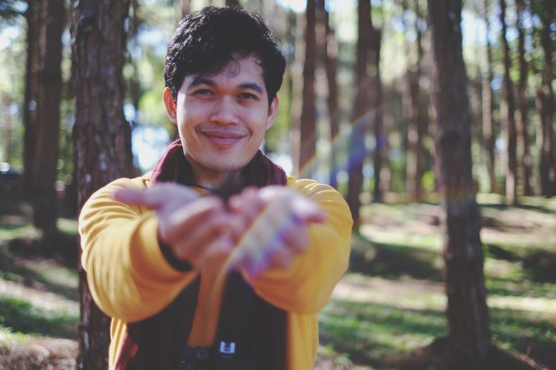 Portrait of smiling young man gesturing in forest