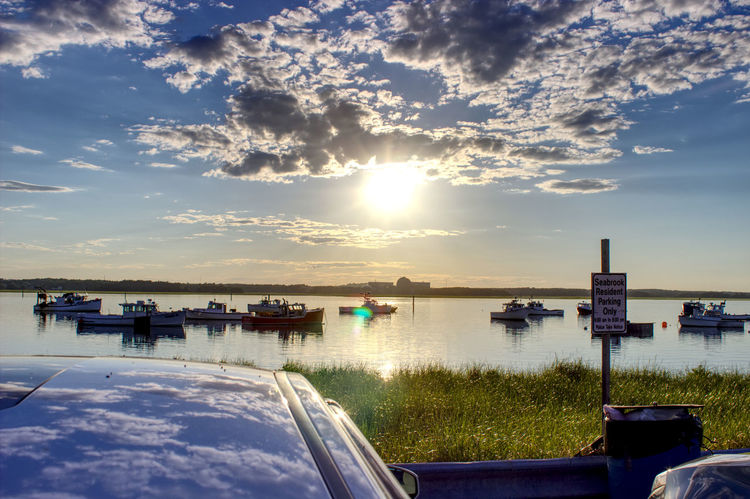 Sunset behind the Seabrook Power Plant Grass Harbor Power Sign Beauty In Nature Car Cloud - Sky Day Moored Nature Nautical Vessel No People Outdoors Reflection Scenics Sea Sky Sun Sunlight Sunset Tranquil Scene Tranquility Transportation Water The Street Photographer - 2018 EyeEm Awards