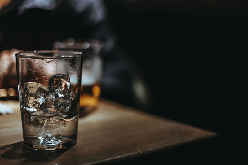 Close-up of ice cube in drinking glass on table