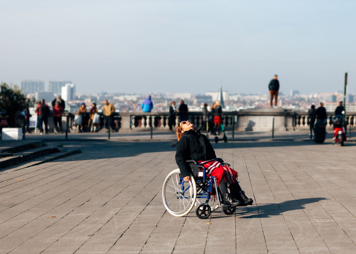 Happy, positive, smiling woman sitting in a wheelchair outdoor in the city