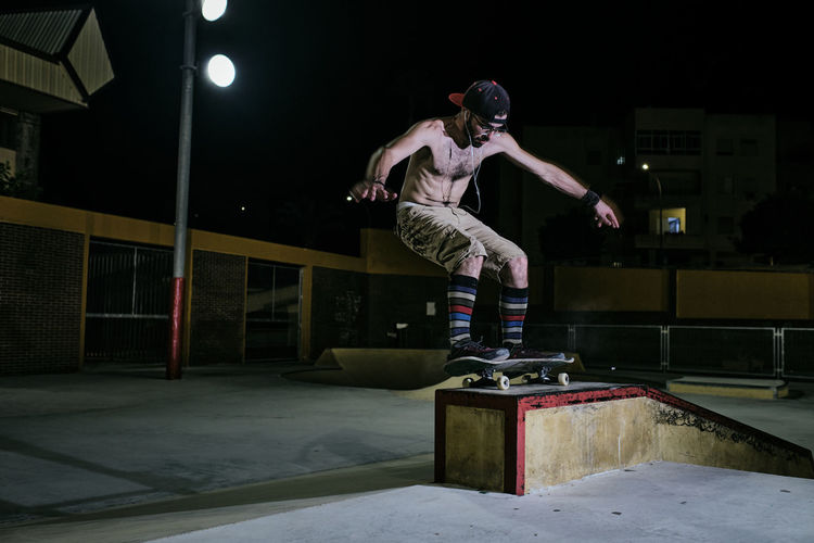 Full length of young man jumping in winter at night