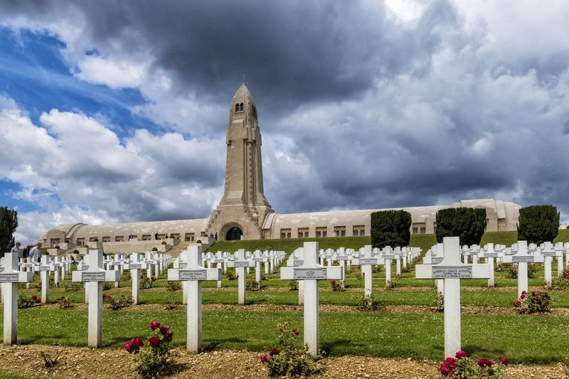 """The Douaumont ossuary (French: L'ossuaire de Douaumont) is a memorial containing the skeletal remains of soldiers who died on the battlefield during the Battle of Verdun in World War I. It is located in Douaumont, France, within the Verdun battlefield. It was built on the initiative of Charles Ginisty, Bishop of Verdun. It has been designated a """"nécropole nationale"""", or """"national cemetery"""" Battle Of Verdun Douaumont Ossuary L'ossuaire De Douaumont Ossuary Cemetery Cloud - Sky Cross Grass Gravestone Graveyard History History Place Memorial Monument Necropolis No People Outdoors Patrotism Religion Sadness Sky Spirituality Tombstone World War 1 World War 1 Memorial"""