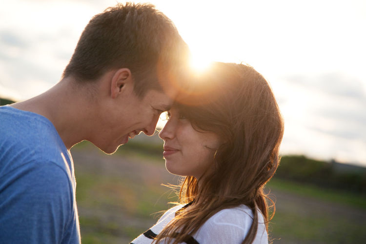 Side view of young couple kissing outdoors