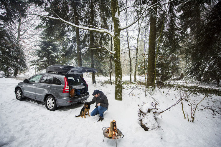 Campfire Camping Hiking Snow ❄ Adult Car Cold Temperature Day Dog Forest Full Length Holiday Land Mode Of Transportation Motor Vehicle Nature One Person Outdoors Plant Snow Togetherness Transportation Tree Warm Clothing Winter