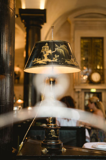 Close-up of illuminated electric lamp on table in restaurant