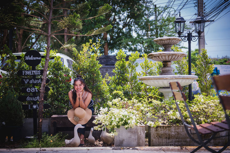 Young woman sitting by potted plants against trees