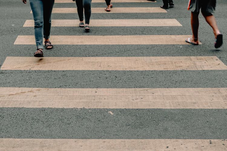 Low section of people walking on zebra crossing