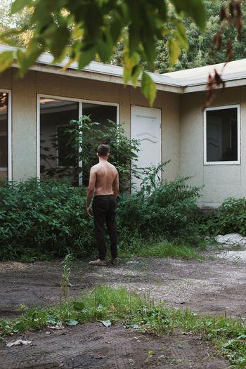 Rear view of shirtless man standing at back yard