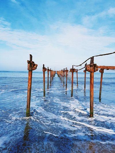 Broken pier over sea against sky