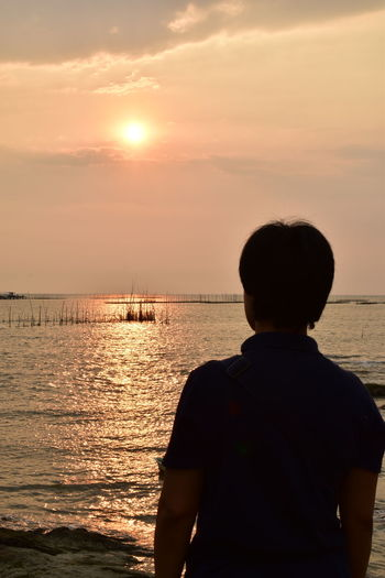 Rear view of man looking at sea against sky during sunset