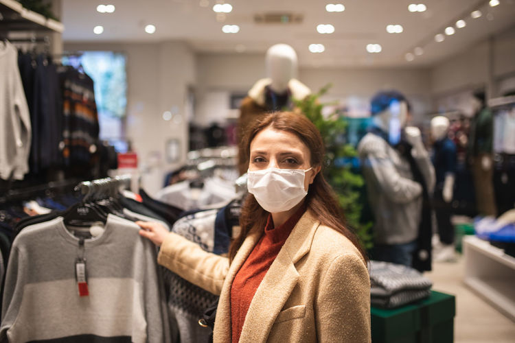 Woman wearing mask while looking at garments