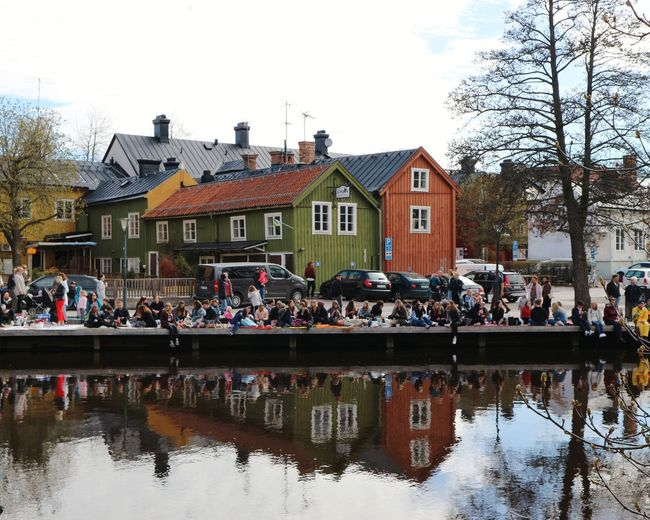 Group of people in canal by buildings in city