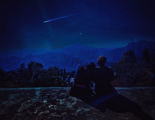 Rear view of couple sitting against sky at night